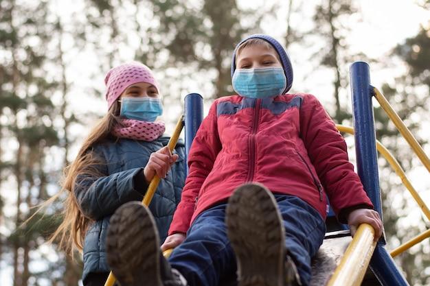 Bambini in maschere mediche nel parco giochi all'aperto mentre la quarantena di coronavirus