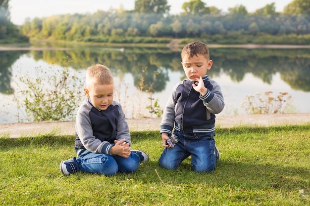 Bambini e concetto di natura. due fratelli seduti sull'erba su sfondo natura