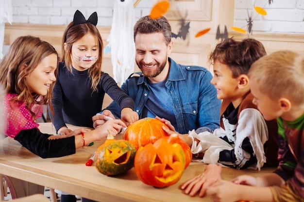 Figli e nipoti. uomo raggiante che invita i suoi figli e nipoti per una festa di halloween incredibile e memorabile
