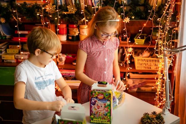 Bambini che aprono i regali di natale. bambina e ragazzo con la scatola attuale di dolci. i bambini aprono regali. i bambini giocano con confezione regalo e caramelle