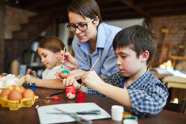 Bambini che verniciano le uova di pasqua