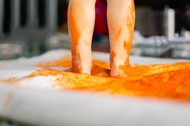Bambini che dipingono immagini con acquarello su carta e realizzano stampe con le mani e i piedi.