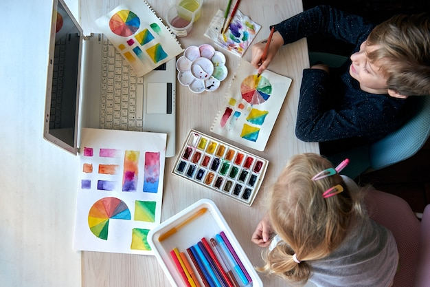 Bambini che dipingono quadri con colori ad acquerello durante la lezione d'arte. gli alunni si stanno concentrando sul disegno con il pennello. ruota dei colori e tavolozza dell'acquerello. lezioni hobby per principianti di teoria del colore