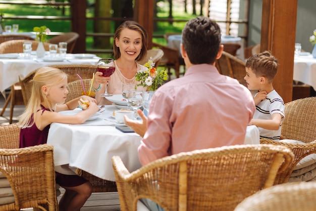 Bambini e genitori. due piccoli bambini biondi si sentono adorabili mentre fanno colazione in famiglia con i genitori