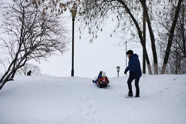 Bambini nel parco in inverno. i bambini giocano con la neve nel parco giochi. scolpiscono pupazzi di neve e scivolano giù per le colline.