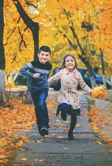 Bambini nel parco con foglie d'autunno. messa a fuoco selettiva.
