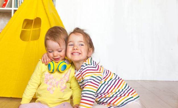 I bambini giocano sul pavimento nella stanza dei bambini. due ragazze raccolgono cubi di legno