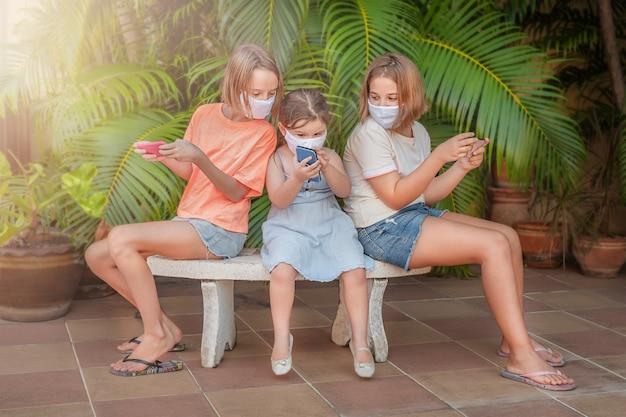 I bambini giocano con i gadget in panchina. le ragazze trascorrono del tempo insieme