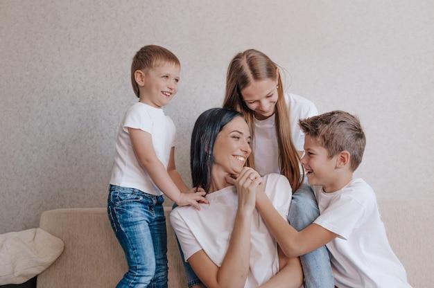 I bambini giocano e giocano con la madre seduta a casa sul divano.