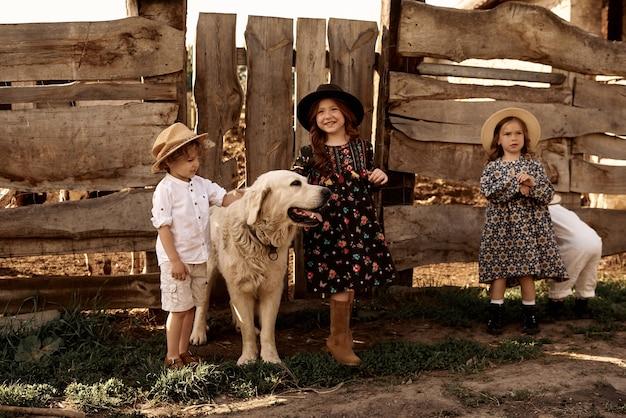 I bambini giocano con un golden retriever nella fattoria