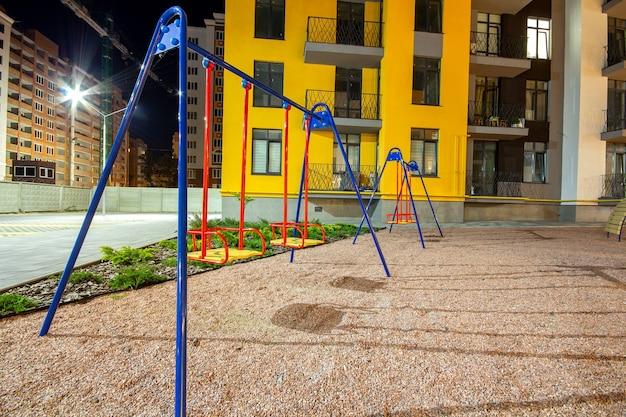 Parco giochi per bambini di notte nel cortile del quartiere residenziale tra condomini.