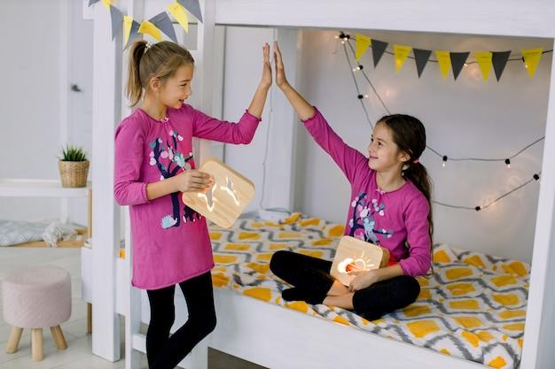 Bambini che giocano in camera da letto. due divertenti ragazze felici di 10 anni, sorelle in pigiama colorato, divertirsi su un letto a castello, tenendo in mano le lampade da notte in legno.