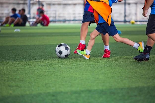 Bambini che giocano a tattiche con il pallone da calcio sul campo in erba con sfondo di allenamento formazione dei bambini nel calcio