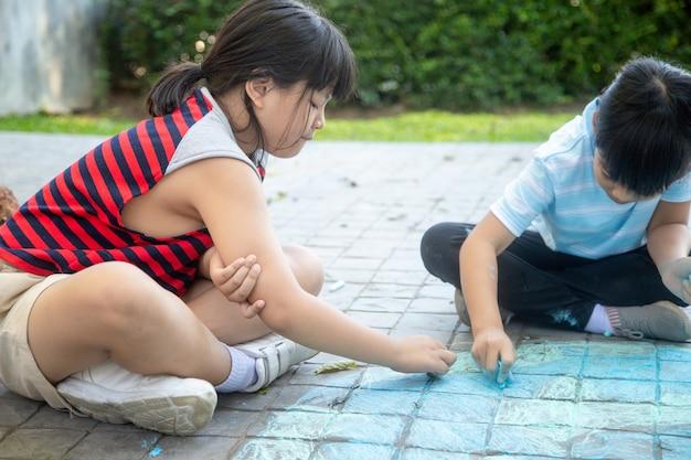 Bambini che giocano con i gessetti colorati