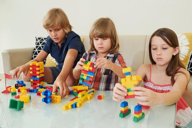 Bambini che giocano con blocchi di plastica colorati
