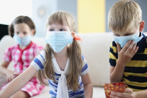 Bambini con maschere mediche protettive che giocano a giochi da tavolo a casa