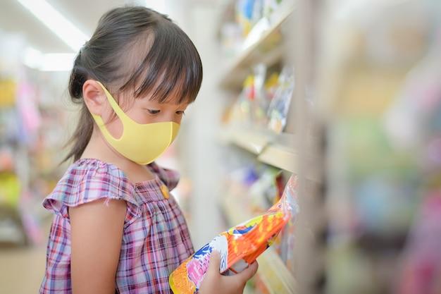 I bambini leggono le etichette dei dolciumi per vedere i componenti e la data di scadenza