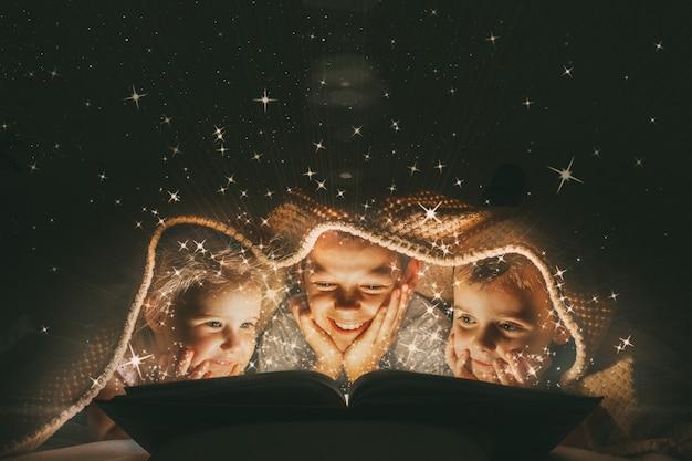 Bambini che leggono un libro sotto una coperta con luce