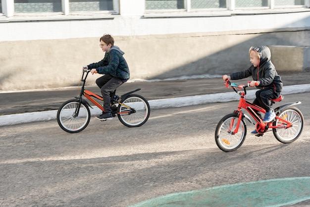 Bambini che vanno in bicicletta sulla strada asfaltata
