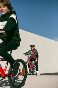 I bambini vanno in bicicletta all'aperto