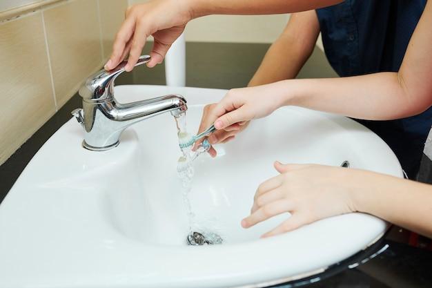 Bambini che risciacquano gli spazzolini da denti