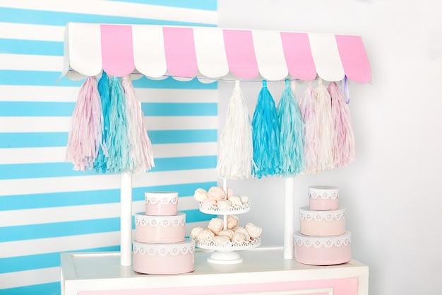 Camera per bambini con striscia blu. zona foto stallo di caramelle con grandi amaretti, caramelle e caramelle gommosa e molle. carrello con gelato. camera decorata per il compleanno. carrello con candy bar.