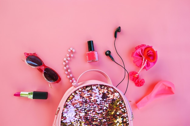 Zaino per bambini con cosmetici e accessori da donna su sfondo rosa. vista dall'alto, piatto.