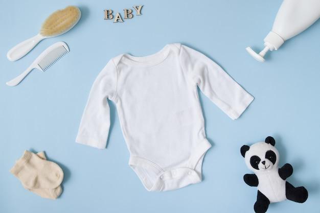Layout piatto di abbigliamento per bambini. di un body bianco per bebè su una superficie blu