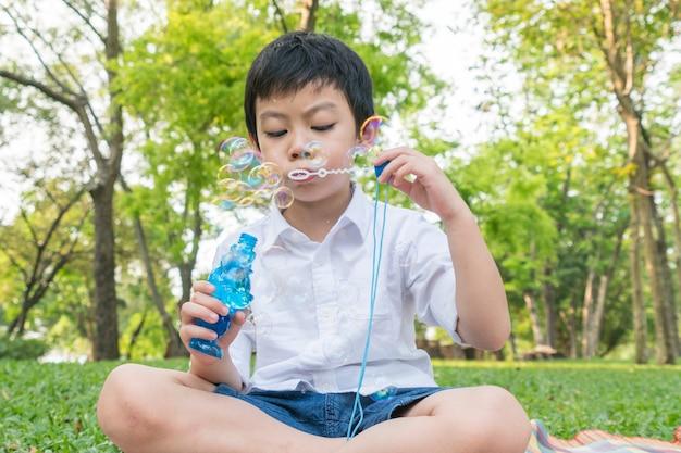 Giorno dei bambini. bolle di sapone di salto del ragazzino del ragazzino nel parco del giardino