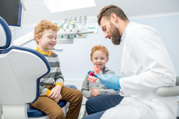 Dentista per bambini che mostra ai ragazzi come lavarsi i denti sulla mascella artificiale presso lo studio dentistico