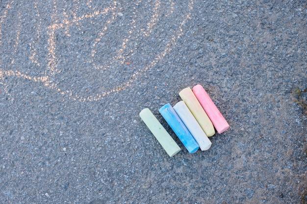 Il disegno dei bambini sulla strada, i pastelli di gesso colorati copiano lo spazio