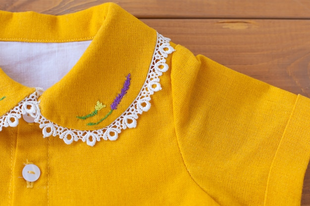 L'abito per bambini è arancione con fiori ricamati sul colletto. abito da festa per bambini.