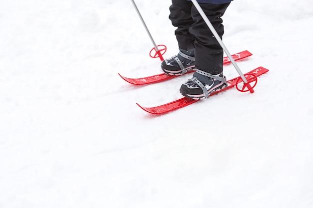I piedi dei bambini con gli sci di plastica rossi con bastoncini attraversano la neve