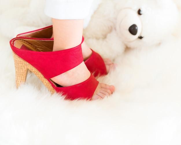 I piedi dei bambini che indossano scarpe con tacco alto contro l'orsacchiotto