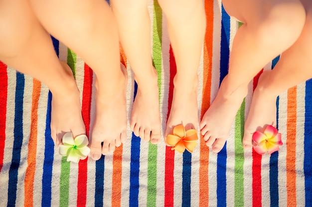 I piedi dei bambini con fiori su sfondo colorato telo da spiaggia spogliato