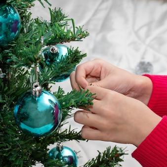 Le mani femminili dei bambini decorano un albero di natale con palline blu, un bambino decora un albero di natale, primo piano. felice anno nuovo e buon natale concetto
