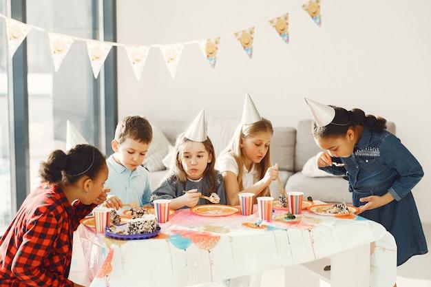 Festa di compleanno divertente per bambini in camera decorata. bambini felici con torta e palloncini.