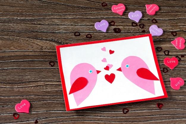 Biglietto di auguri per bambini due uccelli e cuore da una carta il giorno di san valentino.