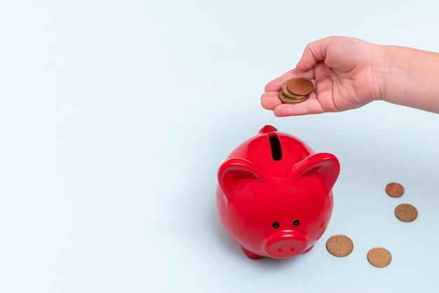 La mano dei bambini tiene diverse monete sopra un salvadanaio rosso accanto a loro su un blu