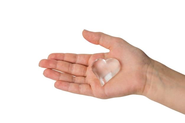 Mano dei bambini con cuore di vetro isolato. un simbolo d'amore.