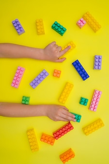 Le mani dei bambini tengono i dettagli del costruttore su uno sfondo giallo.