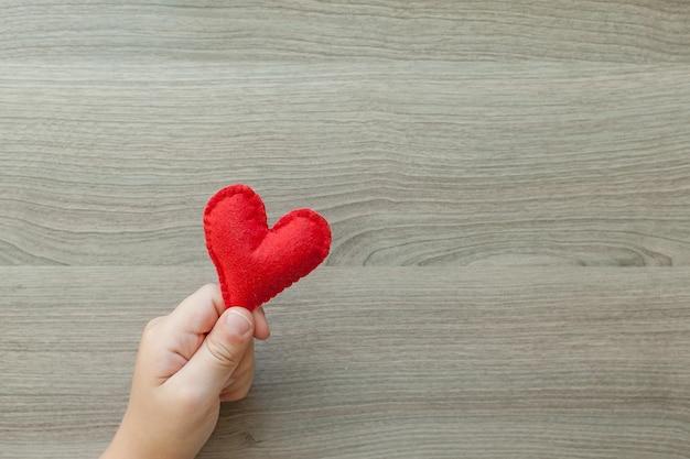 Le mani dei bambini tengono un cuore fatto di feltro.