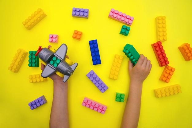 Le mani dei bambini tengono un aereo fatto di parti di design su uno sfondo giallo.