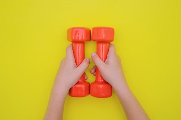 Le mani dei bambini tengono i manubri rossi. il concetto di sport e uno stile di vita sano.