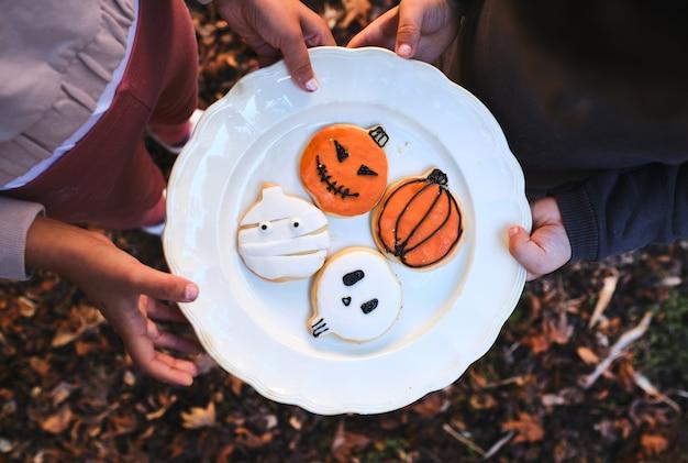 Le mani dei bambini che tengono un piatto di biscotti fatti in casa decorati per halloween