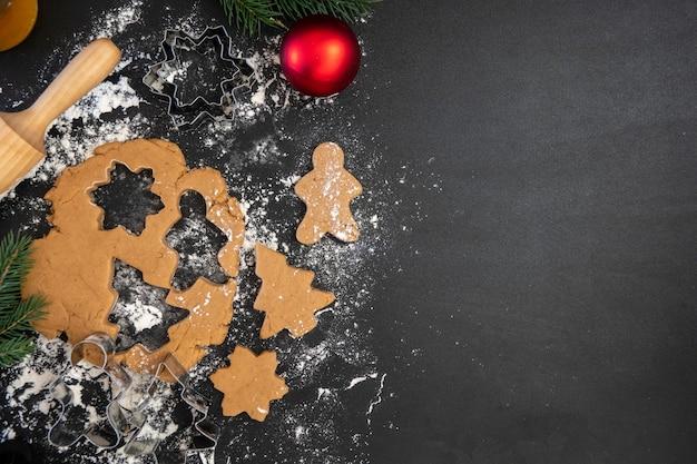 Le mani dei bambini preparano i biscotti di panpepato di capodanno su un tavolo di legno. fare i biscotti con un tagliabiscotti. anno nuovo e concetto di natale.