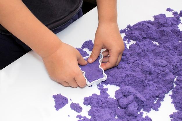 Le mani dei bambini giocano con la sabbia cinetica. concetto di sviluppo delle capacità motorie dei bambini, educazione prescolare.