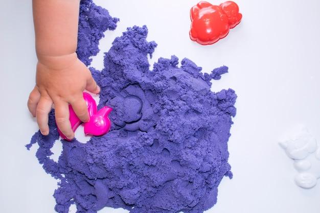 Le mani dei bambini giocano con la sabbia cinetica