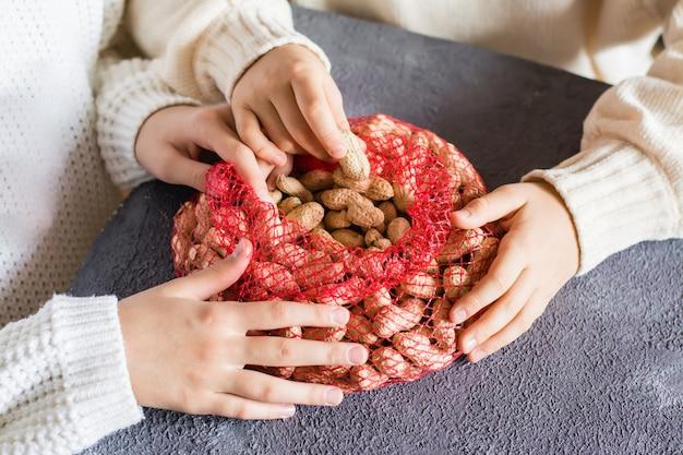 Le mani dei bambini raggiungono le noccioline non sbucciate da un sacchetto a rete sul tavolo. stile di vita