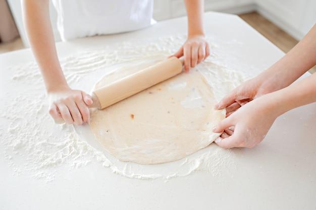 Le mani dei bambini stendono la pasta della pizza su un tavolo bianco. divertirsi insieme in cucina. vista dall'alto